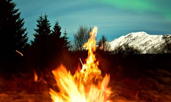Campfire at night against a snow capped mountain backdrop
