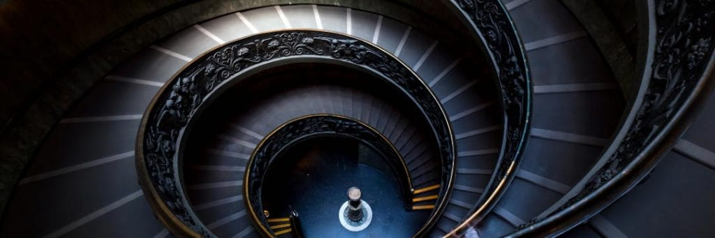 View downwards from top of dark coloured spiral staircase with ornate banister