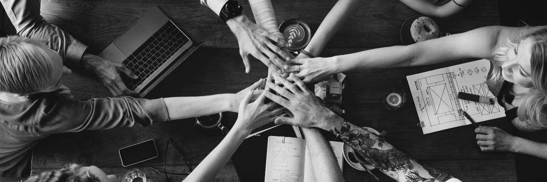 Group of people all holding one hand into the middle of a table