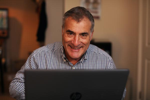 Jeremy Cassell smiling while using a laptop computer