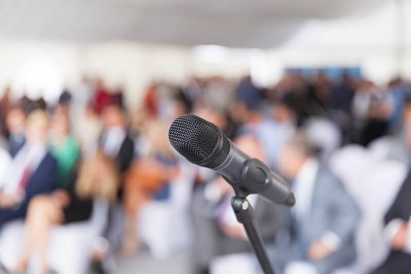 Microphone in front of blurred crowd of seated people