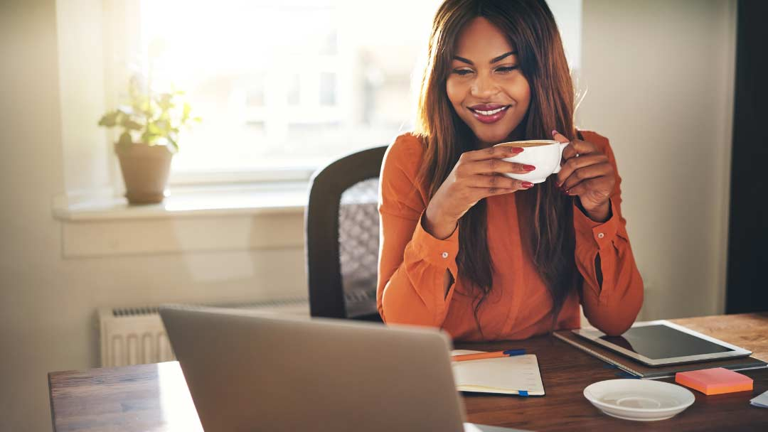 Woman drinking coffee while completing online training
