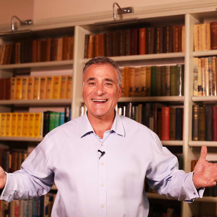 Jeremy Cassell standing infront of a bookcase with arms open