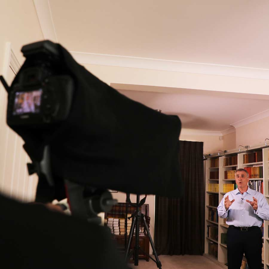 Jeremy Cassell being filmed in a white room infront of a bookcase