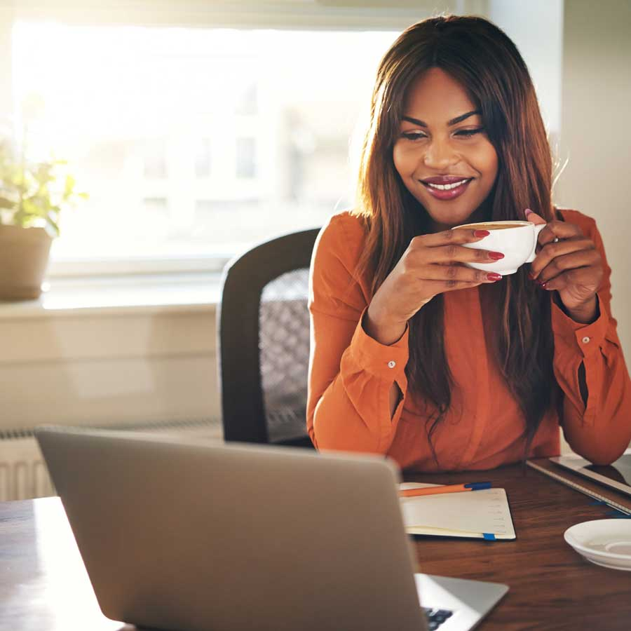 Smiling woman drinking coffee infront of her laptop